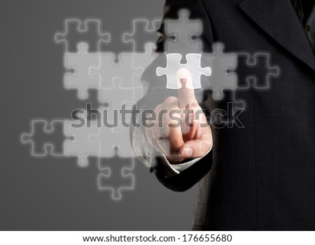 Businessman with jigsaw puzzle on transparent display - solution or network concept - stock photo