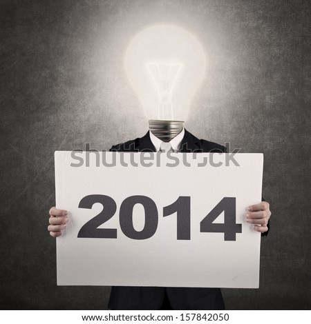 Businessman with lamp-head showing the New Year 2014 - stock photo