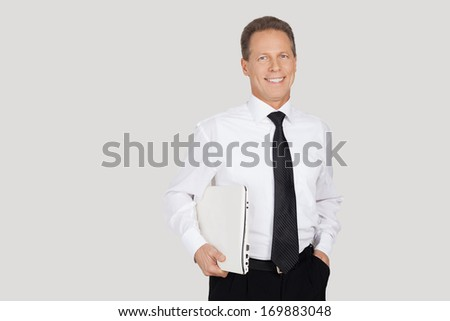 Businessman with laptop. Cheerful senior man in formalwear holding laptop and smiling while standing against grey background