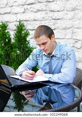 Businessman with laptop in cafe on the street. Makes notes with pen