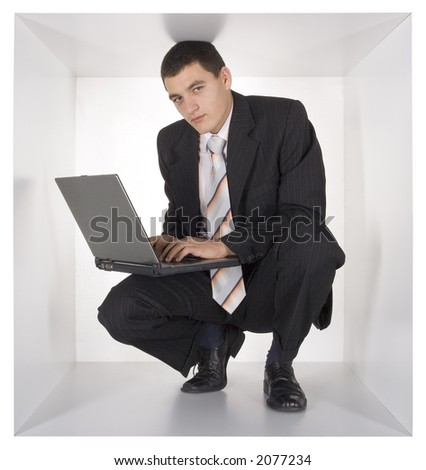 businessman with laptop in the cramped white cube
