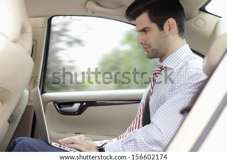 Businessman with laptop on the knee in his car - stock photo
