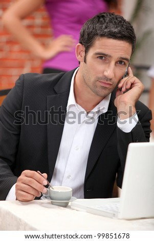 businessman with laptop on the phone having coffee in restaurant - stock photo