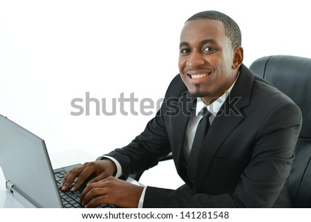 Businessman with laptop sitting at desk - stock photo