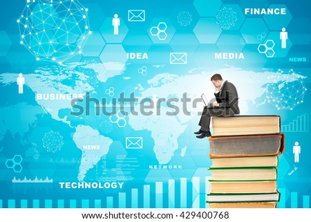 Businessman with laptop sitting on stack of books on blue background with world map - stock photo