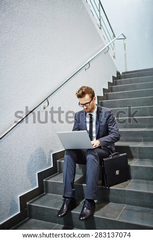 Businessman with laptop sitting on stairs and networking