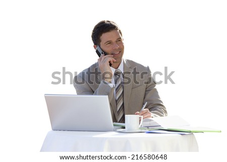 Businessman with laptop talking on cell phone - stock photo
