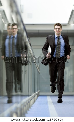 Businessman with laptop under his arm runs along modern office building corridor