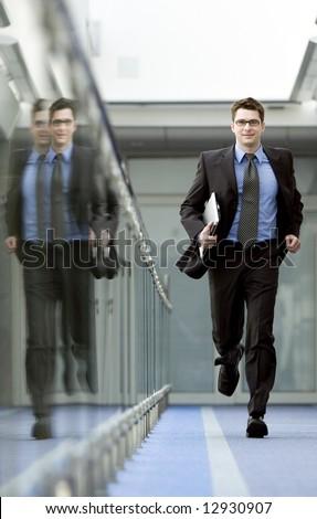 Businessman with laptop under his arm runs along modern office building corridor - stock photo