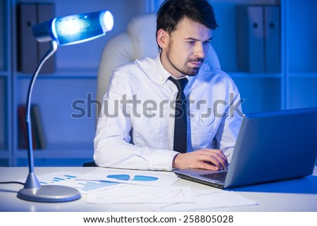Businessman with laptop. Young businessman is looking at laptop in his office. - stock photo