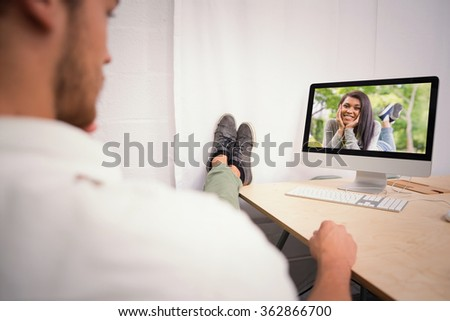 Businessman with legs crossed at ankle on office desk against pretty brunette smiling at camera in park