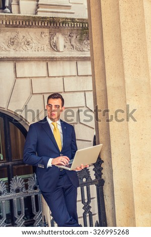 Businessman with little scar on lip - cleft lip, dressing in blue suit, yellow tie, working on laptop computer. Concept of facing reality, up and down, self assured, self esteem, confidence, success.  - stock photo