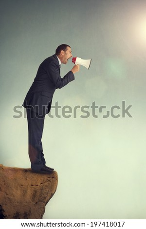 businessman with loudhailer on the edge of a cliff shouting