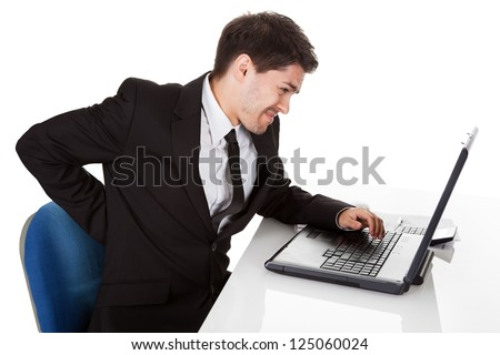 Businessman with lower back ache from sitting with a bad posture in his office chair working on his laptop massaging his back with his hand - stock photo