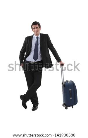 Businessman with luggage stood waiting - stock photo