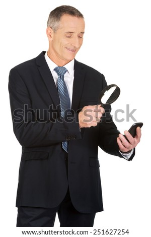 Businessman with magnifying glass and mobile phone. - stock photo