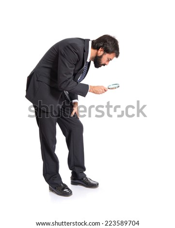 Businessman with magnifying glass over white background - stock photo