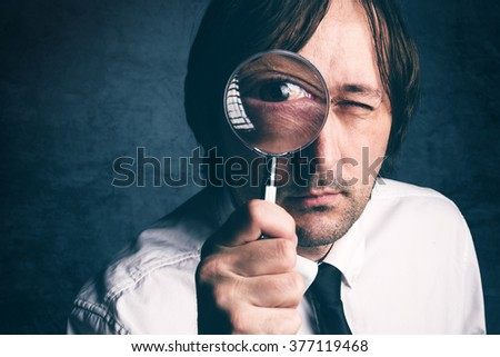 Businessman with magnifying glass, tax inspector doing financial auditing or consultancy, retro toned, selective focus - stock photo