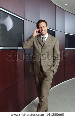 Businessman with mobile phone in front of modern building - stock photo
