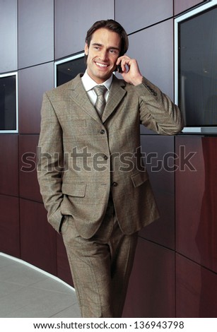 Businessman with mobile phone in modern building - stock photo