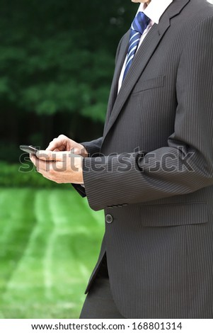 Businessman with mobile phone standing in garden
