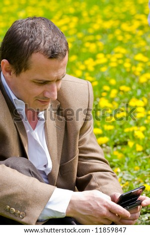 Businessman with mobile technology in a meadow with dandelions