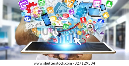 Businessman with modern tablet in his hand and applications flying over - stock photo