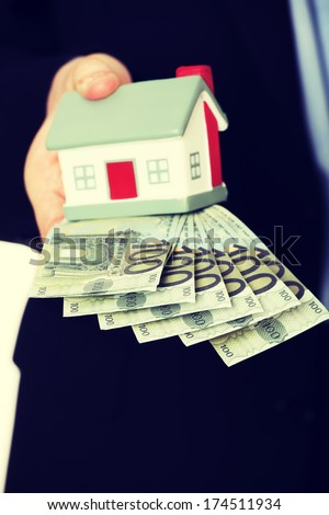 Businessman with money and house's model. Isolated on white background.  - stock photo