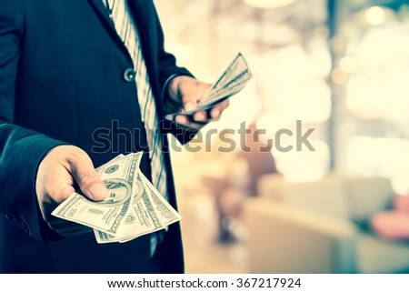 Businessman with money in hand, US dollar (USD) bills - investment, success and profitable business concepts,vintage process style - stock photo