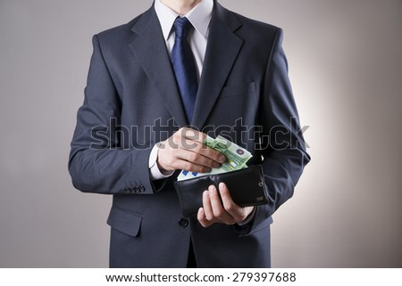 Businessman with money in purse in hands on a gray background - stock photo