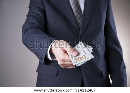 Businessman with money in studio on a gray background. Corruption concept. Hundred dollar bills