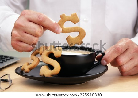 Businessman with money on his mind taking a coffee break - stock photo