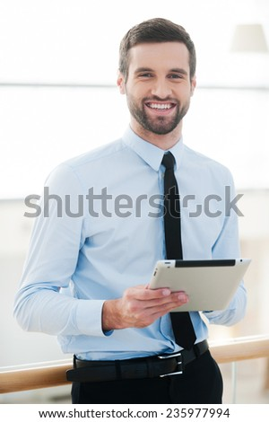 Businessman with note pad. Cheerful young businessman holding digital tablet and smiling while standing indoors - stock photo