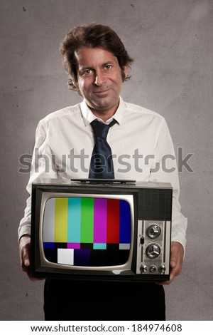 businessman with old retro television on gray background - stock photo