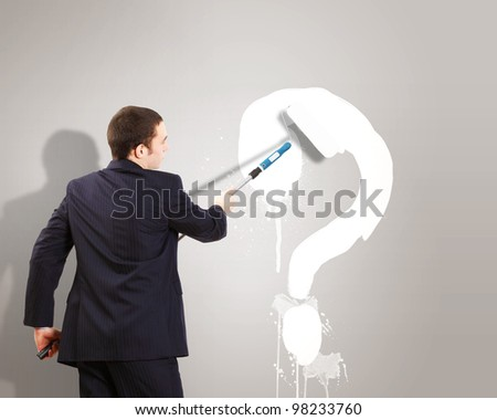 Businessman with paint brash and picture of question mark on the wall - stock photo