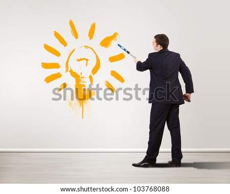 Businessman with paint brush and green energy symbols - stock photo