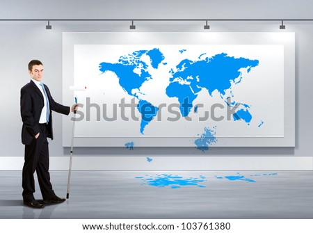 Businessman with paint brush and world map on the background - stock photo