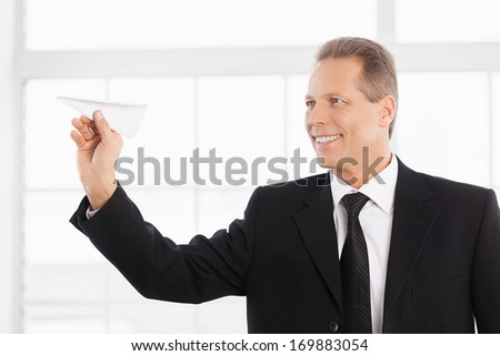 Businessman with paper airplane. Cheerful mature man in formalwear holding paper airplane and smiling - stock photo