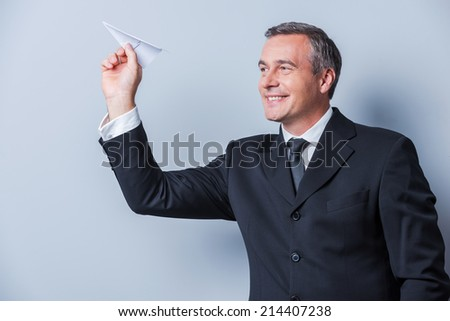 Businessman with paper airplane. Playful mature man in formalwear holding paper airplane and smiling while standing against grey background - stock photo