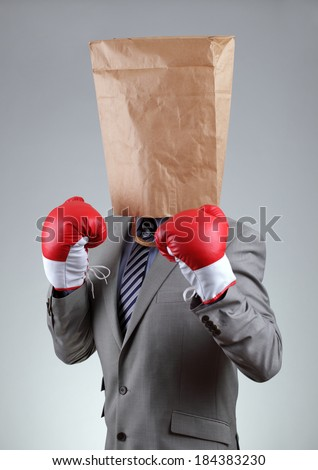 Businessman with paper bag on his head wearing boxing gloves concept for tough business, recruitment or anonymous bullying, copy space on bag