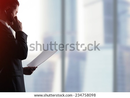 businessman with paper  on a city  background - stock photo