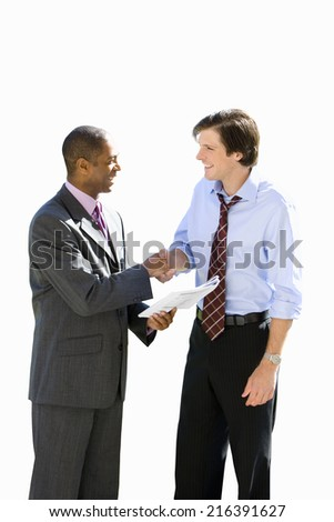 Businessman with paperwork shaking hands with associate, side view, cut out