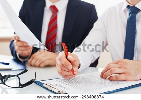 Businessman with pen over contract reading it - stock photo
