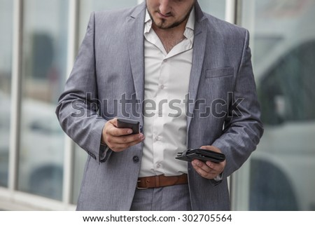 Businessman with phone and wallet in the urban district. Business, job, Finance, cash, electronic payment. - stock photo