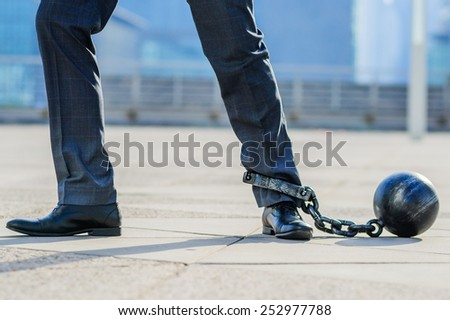 Businessman with prisoner's ball on the leg. - stock photo