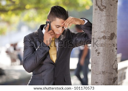 businessman with problems talking at his cellphone next to a tree