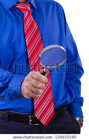 Businessman with red tie and blue shirt holding magnifying glass and examining, isolated on white background. - stock photo