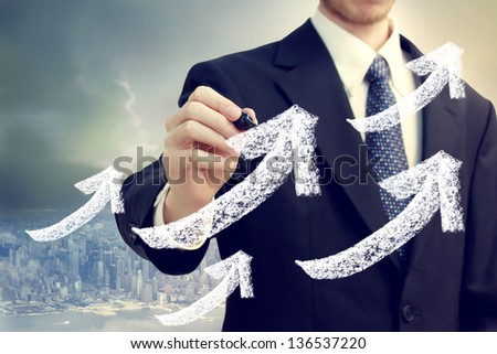 Businessman with rising arrows showing success with big city backdrop - stock photo