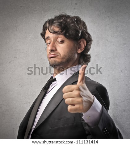 Businessman with satisfied expression and thumbs up - stock photo