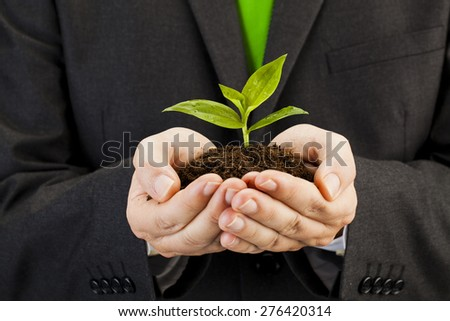 Businessman with seedling in his hands Environment and nature protection concepts - stock photo
